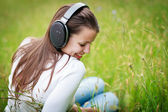 Portrait of a pretty young woman listening to music — Stock Photo