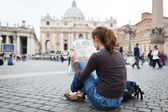 Pretty young female tourist studying a map — Stok fotoğraf