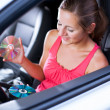 Young female driver playing music in the car (changing CDs) — Stock Photo #7998616