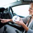 Young female driver playing music in the car (changing CDs) — Stock Photo #7998621