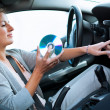 Young female driver playing music in the car (changing CDs) — Stock Photo