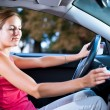 Young female driver playing music in the car (changing CDs) — Stock Photo #7998655