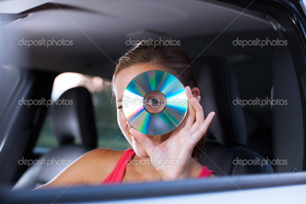 Young female driver playing music in the car (changing CDs)  Stock Photo #7998632
