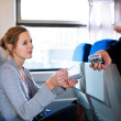 Woman having her ticket checked by the train conductor — Stock Photo