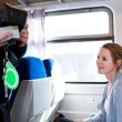 Woman having her ticket checked by the train conductor - Stock Photo