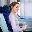 Young woman traveling by train, holding her train ticket — Stock Photo