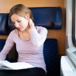 Young woman reading a book while on a train — Stock Photo