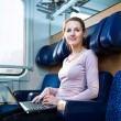 Young woman using her laptop computer while on the train — Stock Photo