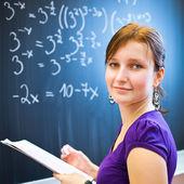 Hezká mladá studentka psaní na tabuli — Stock fotografie
