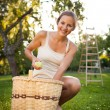 Young woman collecting apples in an orchard — Stock Photo #8520715