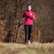 Young woman running outdoors in a city park on a cold fall — Stock fotografie