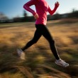 Young woman running outdoors in a city park on a cold fall — Stock Photo