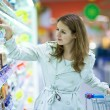 Beautiful young woman shopping in supermarket — Stock Photo #8520930