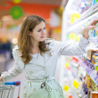 Beautiful young woman shopping in supermarket — Stock Photo #8520934
