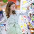 Stock Photo: Beautiful young woman shopping in supermarket