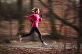 Young woman running outdoors in a city park on a cold fall — Stok fotoğraf