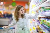 美丽的年轻女子在超市购物 — 图库照片