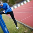 Young woman stretching before her run — Stockfoto