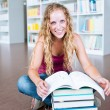 Pretty female college student in a library — Stock Photo