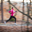 Young woman running outdoors in a city park — Stockfoto