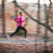 Young woman running outdoors in a city park — Stok fotoğraf
