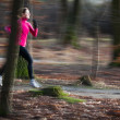 Young woman running outdoors in a city park — ストック写真