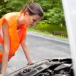 Young female driver bending over the engine of her broken down car — Stock Photo #8666472