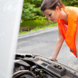 Young female driver bending over the engine of her broken down car — Stock Photo #8666481