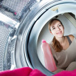 Housework: young woman doing laundry - Stock Photo