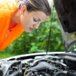 Young female driver bending over the engine of her broken down car — Stock Photo #8666522
