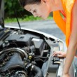 Young female driver bending over the engine of her broken down car — Stock Photo #8666530