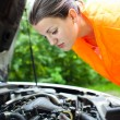 Young female driver  bending over  the engine of her broken down car - Stock Photo