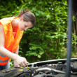 Young female driver bending over the engine of her broken down car — Stock Photo #8666558