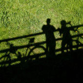 Two mountain bikers' silhouettes during a halt on a bridge — Stock Photo