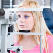 Pretty, young female patient having her eyes examined — Stockfoto