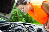 Young female driver bending over the engine of her broken down car — Stock Photo
