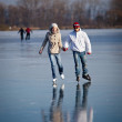 Couple ice skating outdoors on a pond on a lovely sunny winter day — Stock Photo #8874297