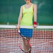 Pretty, young female tennis player on the tennis court - Stock Photo