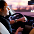 Woman driving his modern car at night in a city - Stok fotoğraf