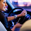 Stock Photo: Woman driving his modern car at night in a city