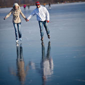 Couple ice skating outdoors on a pond on a lovely sunny winter day — Stok fotoğraf