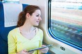 Ung kvinna med sin tablet pc när du reser med tåg — Stockfoto