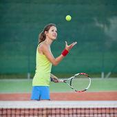 Hübsche, junge tennisspielerin auf dem tennisplatz — Stockfoto