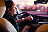 Woman driving his modern car at night in a city — Stock Photo
