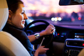 Woman driving his modern car at night in a city — Stok fotoğraf
