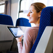 Young woman using her tablet in train — Stok fotoğraf