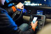 Adam modern arabasını gece bir şehirde sürüş — Stok fotoğraf