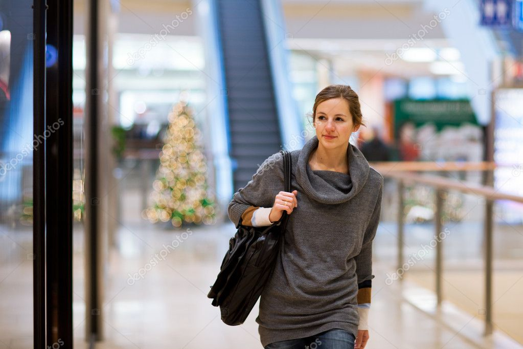 Young woman looking at store windows when shopping in a shopping mall/center  Stock Photo #8874390