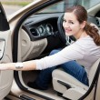 Pretty young woman driving her new car - Foto Stock