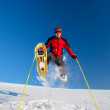 Young man having fun while snowshoeing outdoors — Stock Photo #9115478
